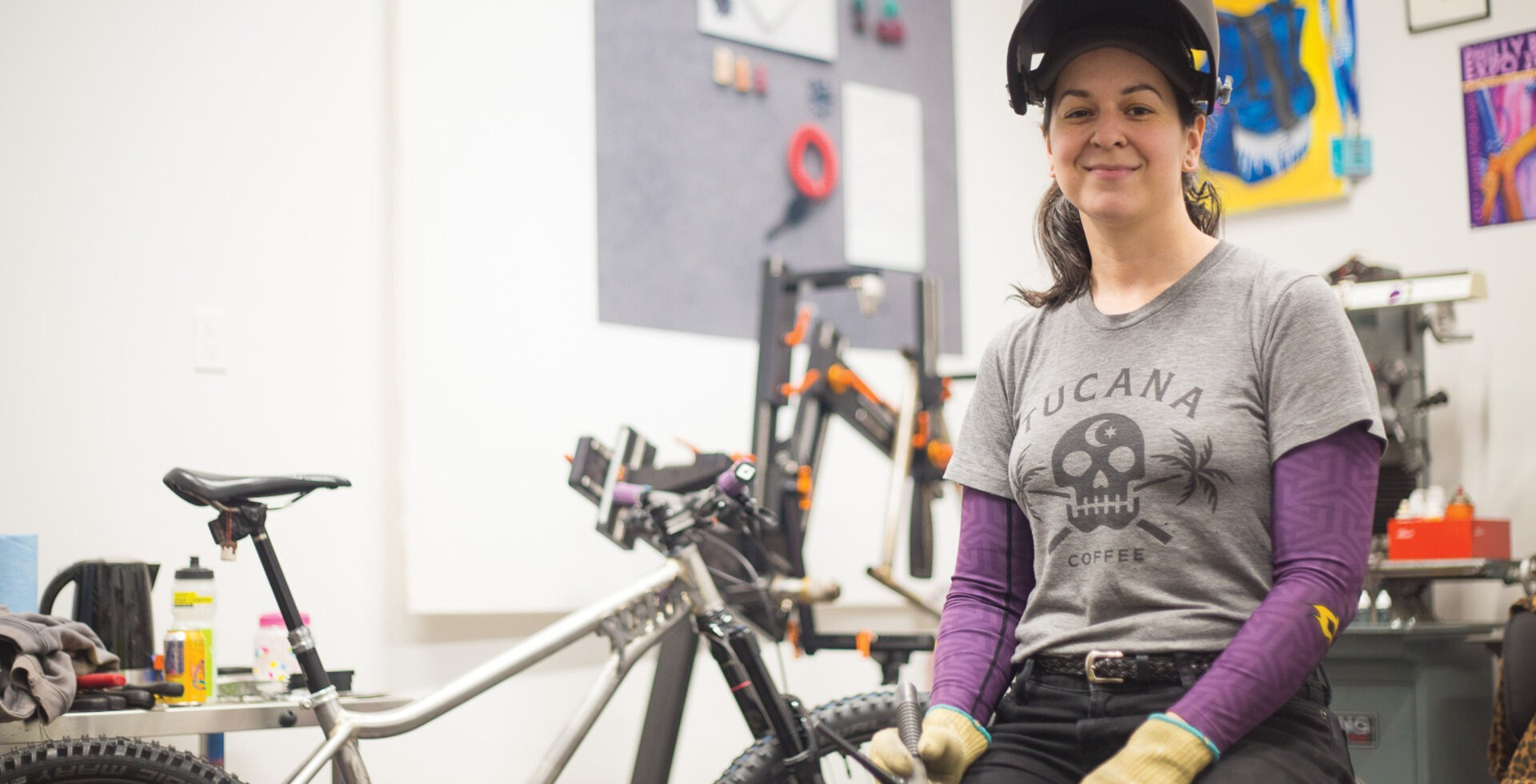 Danielle Schön in her Squamish, BC shop with the bike she built for the 2019 Philly Bike Expo behind her. The hardtail mullet-style bike is the perfect amalgamation of Schön's artistic skills and Squamish's burly riding style.