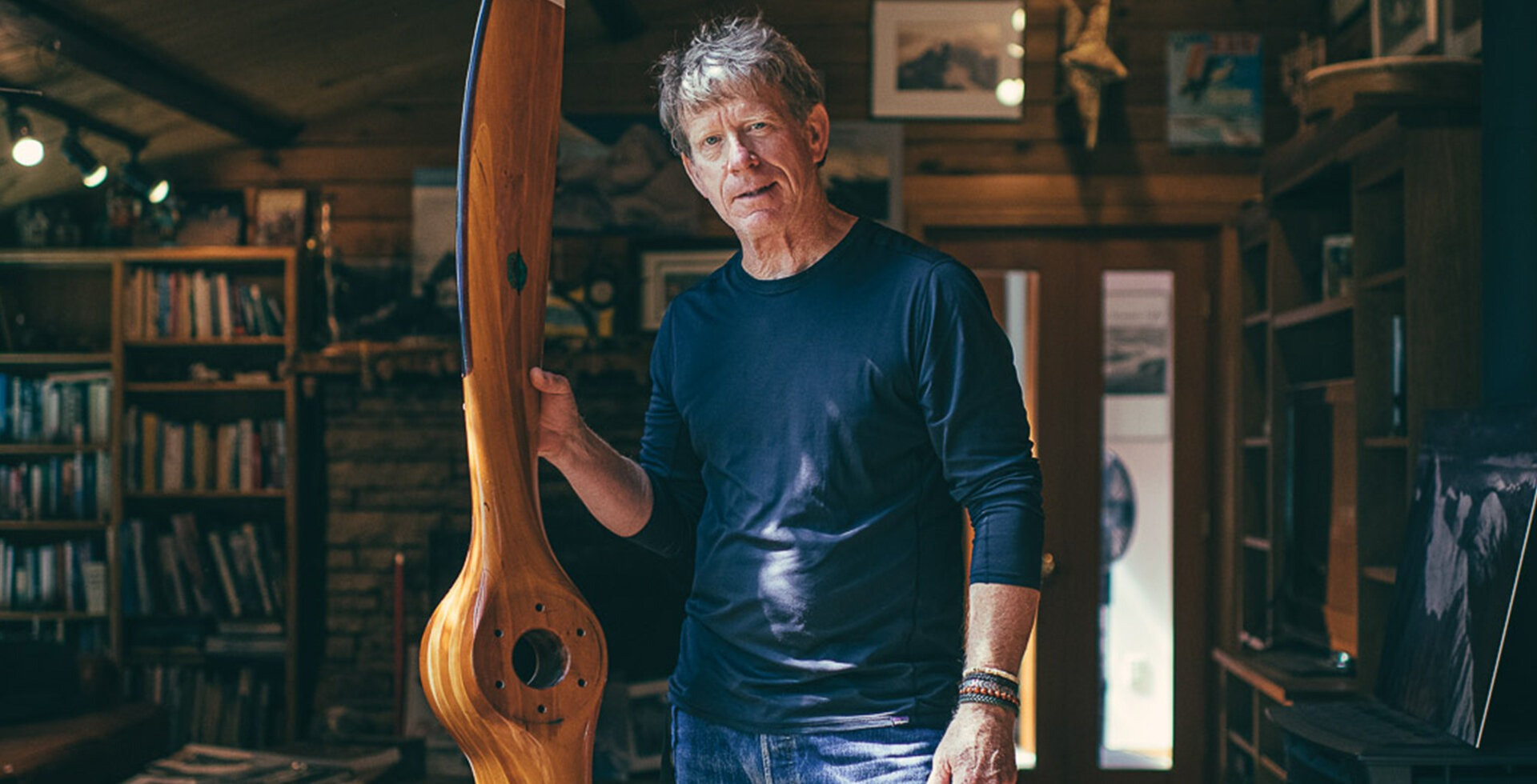 """John Scurlock holds a cherry wood propeller made by his friend Ted Hendrickson. """"I saw it one day in his shop and thought it was a work of art, he sold it to me for $300 and it's been hanging on my living room wall ever since,"""" John says."""